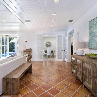 Foto di un soggiorno classico di medie dimensioni e stile loft con pareti bianche, pavimento in terracotta, nessun camino, TV a parete e pavimento rosso