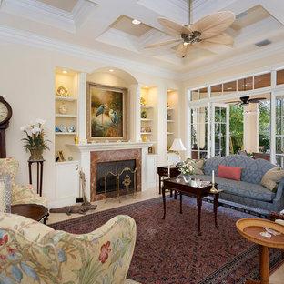 他の地域の中くらいのトロピカルスタイルのおしゃれな独立型リビング (フォーマル、ベージュの壁、磁器タイルの床、標準型暖炉、漆喰の暖炉まわり、テレビなし、ベージュの床) の写真