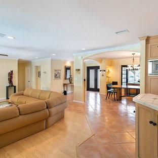 Esempio di un soggiorno tradizionale di medie dimensioni e aperto con sala formale, pareti gialle, nessun camino, nessuna TV, pavimento rosso e pavimento in terracotta