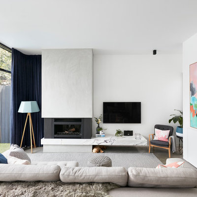 Living room - contemporary enclosed concrete floor living room idea in Melbourne with white walls, a standard fireplace, a concrete fireplace and a wall-mounted tv