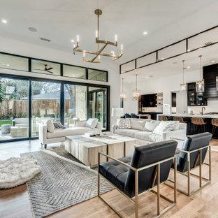 Esempio di un soggiorno moderno aperto con pareti bianche, parquet chiaro, camino classico, cornice del camino in intonaco, TV a parete e pavimento marrone