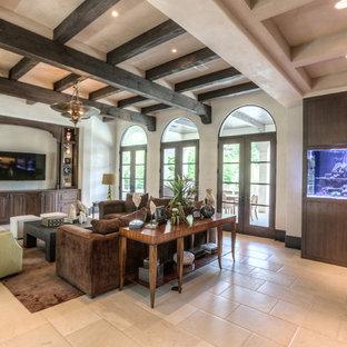 ヒューストンの大きい地中海スタイルのおしゃれな独立型リビング (フォーマル、白い壁、ライムストーンの床、暖炉なし、壁掛け型テレビ、ベージュの床) の写真