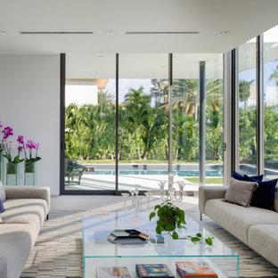 Immagine di un soggiorno design con pareti bianche, pavimento in pietra calcarea e pavimento beige