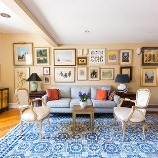Modelo de salón tradicional con paredes beige, suelo de madera en tonos medios y suelo marrón