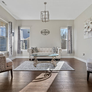 Example of a classic enclosed dark wood floor and brown floor living room design in Charlotte with beige walls