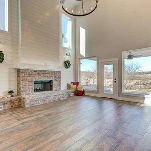 オクラホマシティの大きいカントリー風おしゃれなLDK (マルチカラーの壁、無垢フローリング、標準型暖炉、レンガの暖炉まわり、茶色い床) の写真