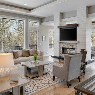 ミネアポリスのトランジショナルスタイルのおしゃれなLDK (グレーの壁、無垢フローリング、両方向型暖炉、石材の暖炉まわり、壁掛け型テレビ、ベージュの床、折り上げ天井) の写真