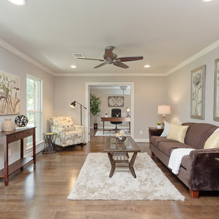 This is an example of a classic living room in Houston with grey walls and medium hardwood flooring.