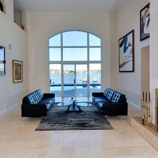 他の地域の中くらいの地中海スタイルのおしゃれなリビングロフト (フォーマル、ベージュの壁、大理石の床、標準型暖炉、タイルの暖炉まわり、テレビなし、ベージュの床) の写真