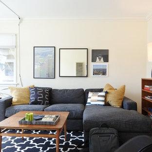 Immagine di un piccolo soggiorno moderno chiuso con pareti bianche, moquette, TV a parete e pavimento grigio
