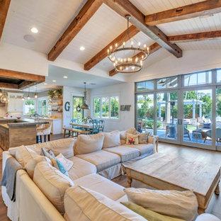 Foto di un soggiorno country aperto con pareti bianche, pavimento in legno massello medio, pavimento marrone e travi a vista