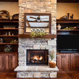 Idee per un grande soggiorno stile americano aperto con pareti beige, pavimento in legno massello medio, camino classico, cornice del camino in pietra, parete attrezzata e pavimento marrone