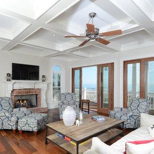 他の地域の大きいビーチスタイルのおしゃれなLDK (標準型暖炉、レンガの暖炉まわり、壁掛け型テレビ、白い壁、無垢フローリング、マルチカラーの床) の写真