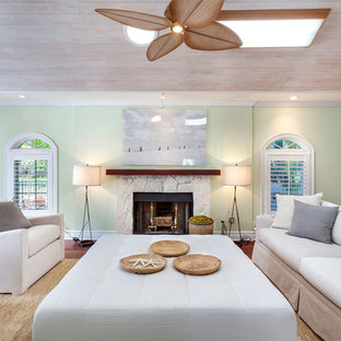 Mid-sized beach style enclosed medium tone wood floor and red floor living room photo in Miami with green walls, a standard fireplace, a stone fireplace and no tv