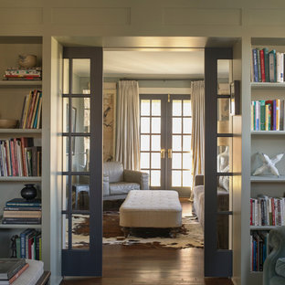 Inspiration for a farmhouse enclosed medium tone wood floor living room library remodel in New York with gray walls