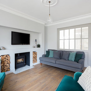 Photo of a classic living room in London with white walls, medium hardwood flooring, a wood burning stove, a wall mounted tv and brown floors.