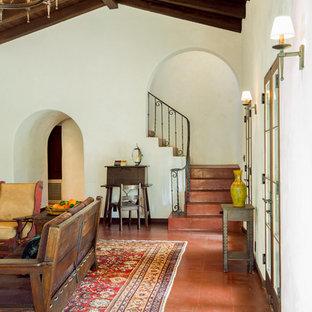 フェニックスの巨大なサンタフェスタイルのおしゃれな独立型リビング (フォーマル、白い壁、コンクリートの床、標準型暖炉、漆喰の暖炉まわり、テレビなし、赤い床) の写真