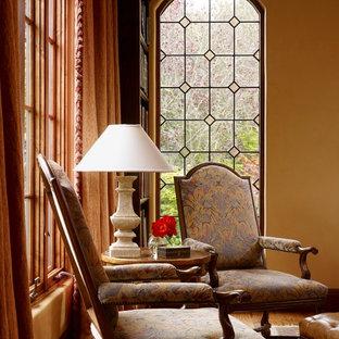 Inredning av ett klassiskt mellanstort allrum med öppen planlösning, med ett bibliotek, mellanmörkt trägolv och orange väggar
