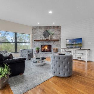 Diseño de salón abierto, de estilo de casa de campo, pequeño, con paredes beige, suelo de madera en tonos medios, chimenea de esquina, marco de chimenea de ladrillo, televisor independiente y suelo marrón