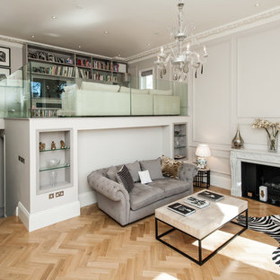 Example of a large classic formal medium tone wood floor living room design in Surrey with beige walls and a standard fireplace