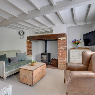 Photo of a small farmhouse enclosed living room in Kent with white walls, carpet, a wood burning stove, a wall mounted tv and beige floors.