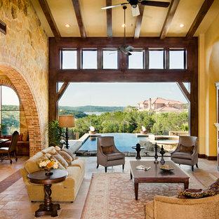 Ejemplo de salón para visitas abierto, mediterráneo, grande, sin televisor, con paredes beige, chimenea tradicional, suelo de baldosas de cerámica, marco de chimenea de piedra y suelo beige