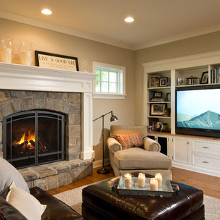 Photo of a traditional living room in New York with a library, a standard fireplace, a stone fireplace surround and a built-in media wall.