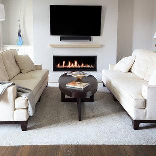 ローリーの小さいトラディショナルスタイルのおしゃれなLDK (フォーマル、グレーの壁、濃色無垢フローリング、吊り下げ式暖炉、壁掛け型テレビ、グレーの床) の写真