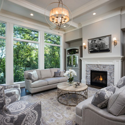 Inspiration for a large transitional formal and open concept dark wood floor and brown floor living room remodel in Minneapolis with gray walls, a standard fireplace, a stone fireplace and a wall-mounted tv