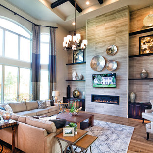 Example of a large classic open concept light wood floor living room design in Dallas with multicolored walls, a hanging fireplace, a tile fireplace and a wall-mounted tv