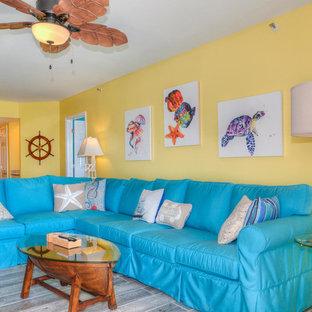 他の地域のビーチスタイルのおしゃれなLDK (黄色い壁、無垢フローリング、据え置き型テレビ) の写真