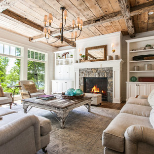 This is an example of a country formal open concept living room with white walls, medium hardwood floors, a standard fireplace, a stone fireplace surround, no tv and brown floor.