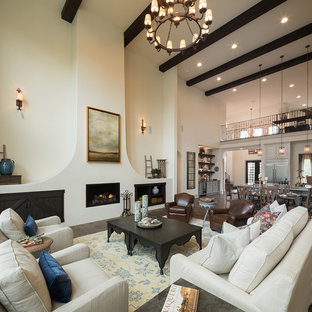 Example of a tuscan formal and open concept dark wood floor and brown floor living room design in Austin with white walls, a standard fireplace, a metal fireplace and no tv