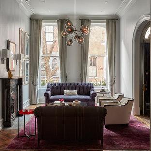 Пример оригинального дизайна: гостиная комната в викторианском стиле с белыми стенами, паркетным полом среднего тона, стандартным камином и фиолетовым полом