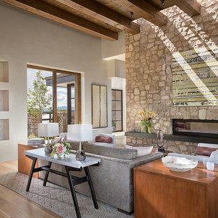 アルバカーキの広いサンタフェスタイルのおしゃれなLDK (白い壁、無垢フローリング、両方向型暖炉、石材の暖炉まわり、茶色い床、埋込式メディアウォール) の写真