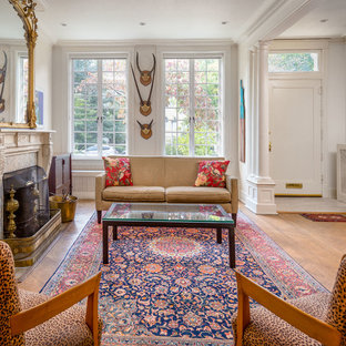 ワシントンD.C.のエクレクティックスタイルのおしゃれなLDK (フォーマル、白い壁、無垢フローリング、標準型暖炉、オレンジの床) の写真