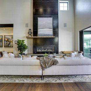 Immagine di un ampio soggiorno country aperto con pareti bianche, pavimento in legno massello medio, camino classico, cornice del camino in metallo, nessuna TV e pavimento marrone