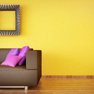 Immagine di un piccolo soggiorno design aperto con pareti gialle, parquet chiaro, sala formale, nessun camino, nessuna TV e pavimento marrone