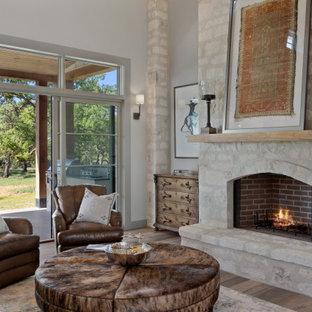 オースティンの広いカントリー風おしゃれなLDK (グレーの壁、淡色無垢フローリング、標準型暖炉、石材の暖炉まわり、グレーの床、板張り天井) の写真