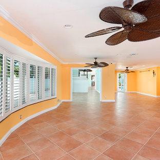 マイアミの巨大なビーチスタイルのおしゃれな独立型リビング (黄色い壁、テラコッタタイルの床、暖炉なし、テレビなし、ピンクの床) の写真