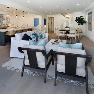 オレンジカウンティの中サイズのビーチスタイルのおしゃれなLDK (フォーマル、白い壁、淡色無垢フローリング、標準型暖炉、コンクリートの暖炉まわり、テレビなし、グレーの床) の写真
