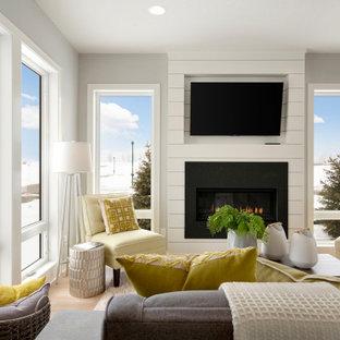 Idée de décoration pour un salon tradition ouvert avec un mur gris, un sol en bois clair, une cheminée standard, un manteau de cheminée en lambris de bois et un téléviseur fixé au mur.