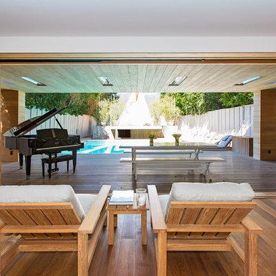 Living room - modern medium tone wood floor living room idea in Los Angeles with a music area