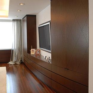 Modelo de salón abierto, minimalista, grande, sin chimenea, con paredes blancas, suelo de madera oscura, televisor colgado en la pared y suelo rojo