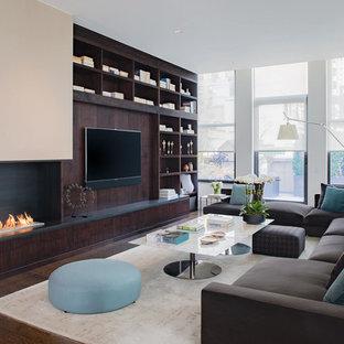 Ejemplo de salón abierto, contemporáneo, grande, con paredes blancas, suelo de madera en tonos medios, chimenea de esquina, marco de chimenea de metal, pared multimedia y suelo marrón