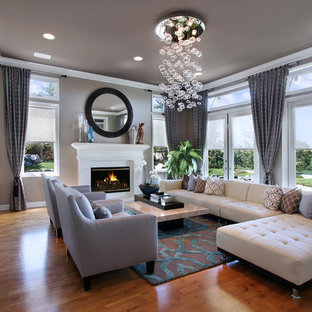 Example of a mid-sized trendy formal and open concept medium tone wood floor and brown floor living room design in Orange County with gray walls, a standard fireplace, a wood fireplace surround and no tv