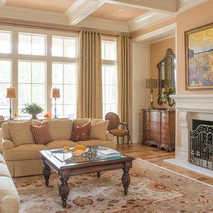 Foto de salón para visitas abierto, tradicional, grande, con parades naranjas, suelo de madera en tonos medios, chimenea tradicional y marco de chimenea de yeso