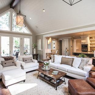 Diseño de salón abierto, clásico renovado, de tamaño medio, con paredes grises, suelo de madera oscura, chimenea tradicional, marco de chimenea de piedra, pared multimedia y suelo marrón