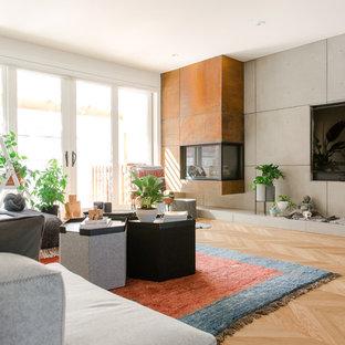 Esempio di un soggiorno design con pareti grigie, parquet chiaro, camino ad angolo, cornice del camino in metallo, TV a parete e pavimento beige