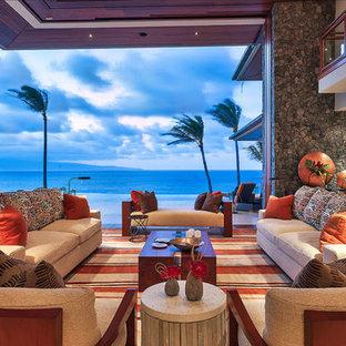 ハワイの巨大なビーチスタイルのおしゃれなLDK (グレーの壁、トラバーチンの床、埋込式メディアウォール、白い床) の写真